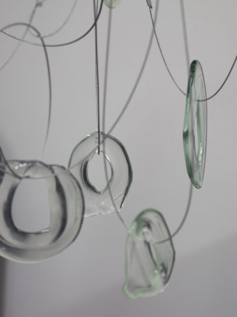 Doughnut shaped clear glass forms dangling from looped wires